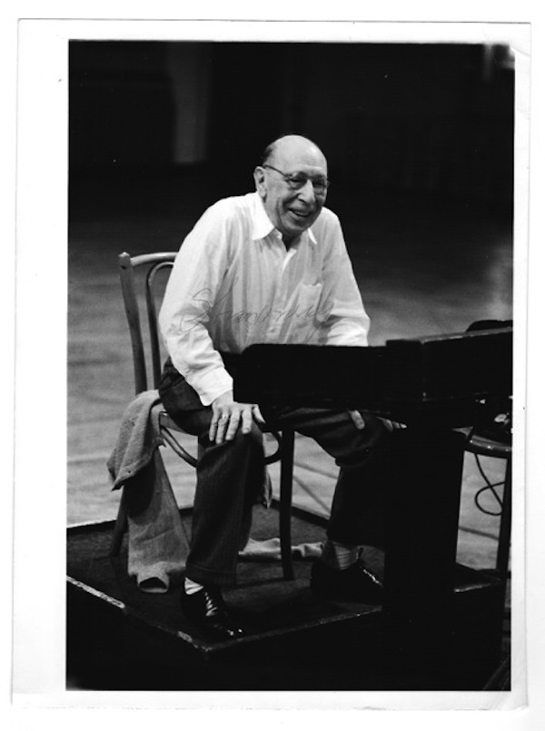 Full length portrait of the composer in his later years, seated at a lectern, shirtcollar open, jacket on the chair behind him, signed by him across the white shirt. Igor Stravinsky, later an exile to France Russian composer, the United States.