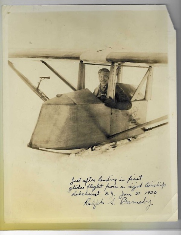 """black and white photo of Ralph S. Barnaby in the cockpit of a glider, inscribed by him below the image """"Just after landing in first / glider flight from a rigid airship / Lakehurst, N.J. Jan. 31, 1930 / Ralph S. Burnaby."""" Ralph S. Barnaby."""